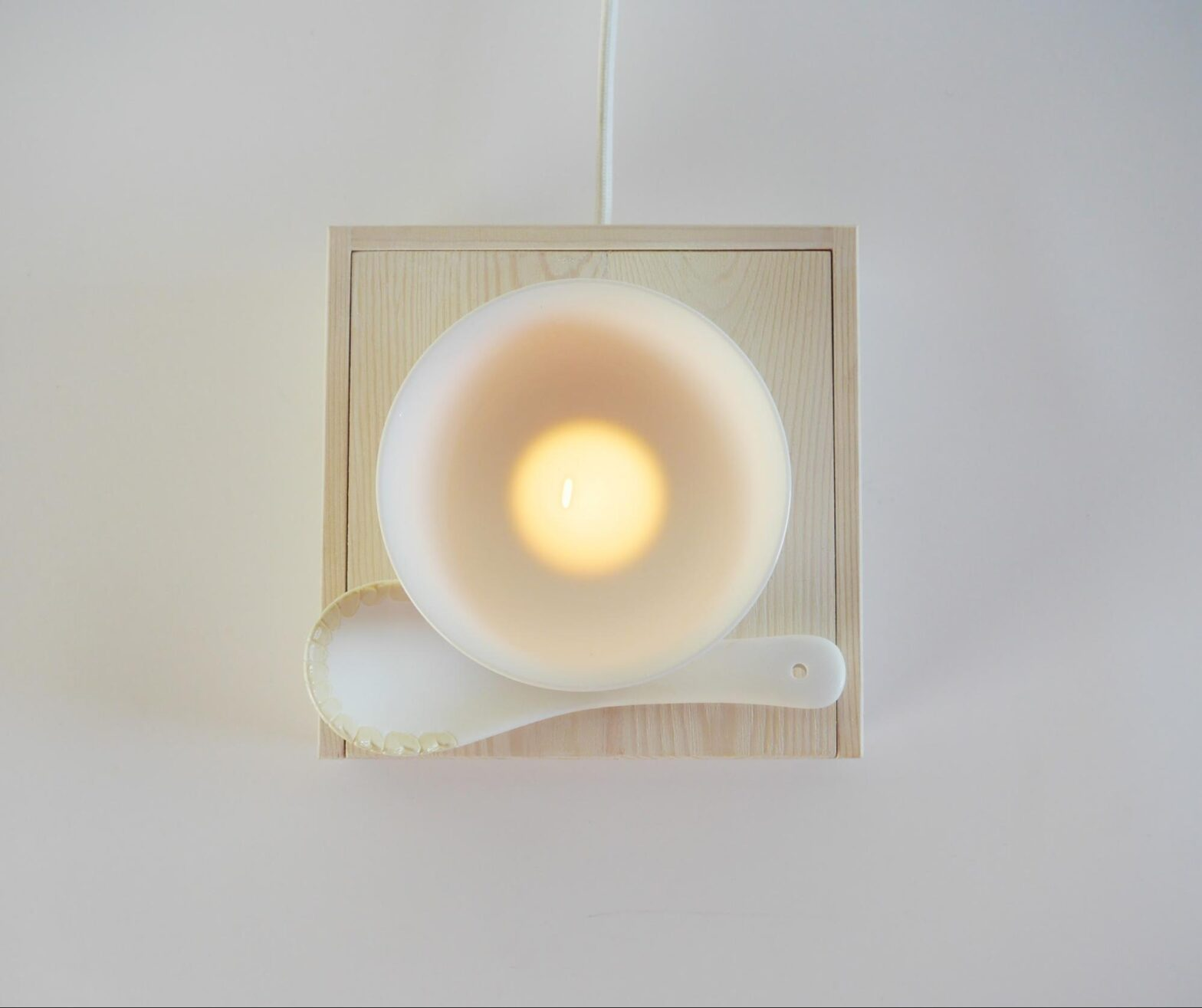 Frank Lee, The Last Grain, 2019. 15 cm x 15 cm, Porcelain spoon and bowl on wooden light box. Height variable, 5 unique pieces in series..